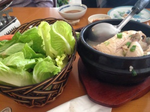 Samgyetang sitting to the right of some crunchy lettuce